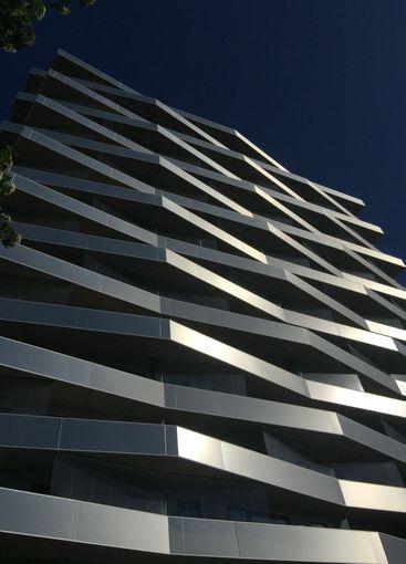 Modern byggnad med stålprofil balkonger sett underifrån.