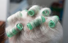 plastic rollers on head of old woman with...