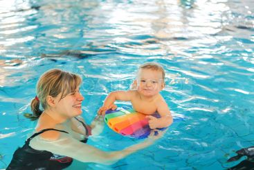 Little baby boy and his mother learning to swim in an...