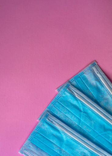 Medical blue protective masks on a pink background
