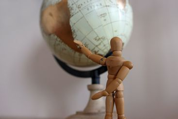 Close up of wooden mannequin pointing at globe with copy...