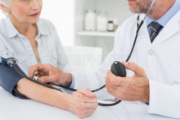 Mid section of doctor taking blood pressure of his patient