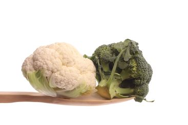 Broccol and a mini cauliflower on a wooden spoon