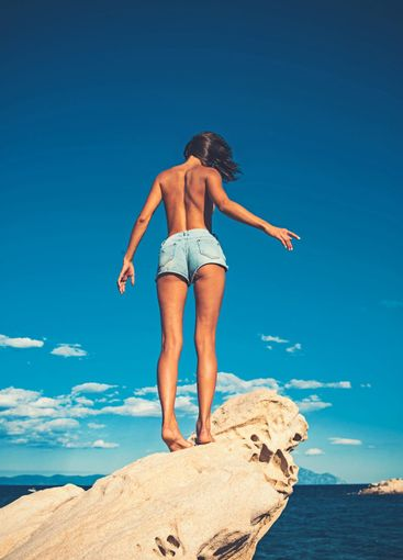sexy woman in jeans shorts on blue sky background. Girl...