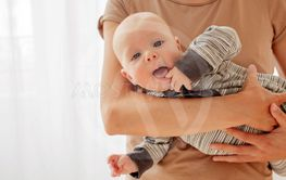 Curious cheeky baby on hands of mother