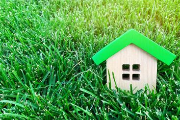 Miniature wooden house on green grass. Real estate...