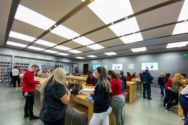 An Apple store with people waiting to purchase Apple...