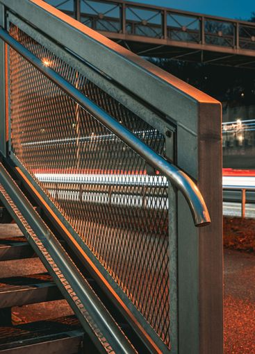 Railing on stairway in front of light trails