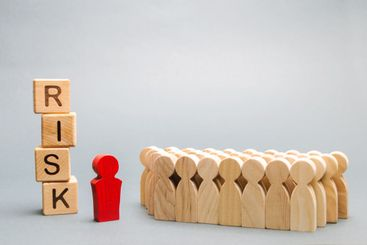 Wooden blocks with the word Risk and a team with a...