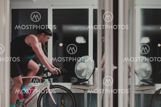 Man cycling on the machine trainer he is exercising in...