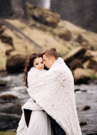 A wedding couple stands on the shore of a mountain river...