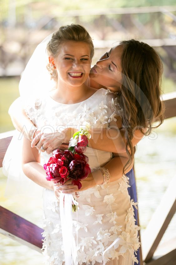 portrait of cute bridesmaid kissing laughing bride in cheek