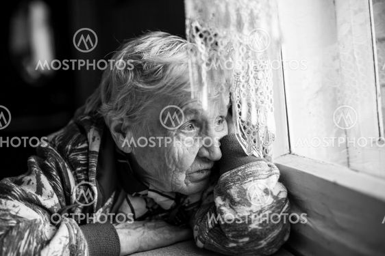 Granny older woman sadly looking out the window.