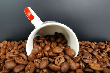 Cup of coffee with roasted brown coffee beans