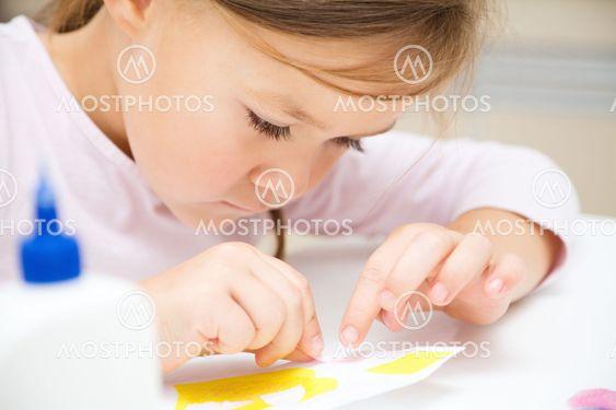 Liten flicka som gör konst och hantverk i förskola