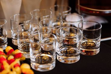 glasses with cognac, whiskey stand on the bar. a lot of...