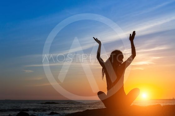 Meditation girl on the ocean during sunset. Yoga...