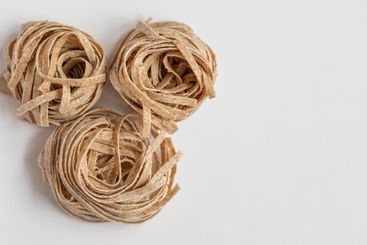 Raw whole grain brown pasta on a white background