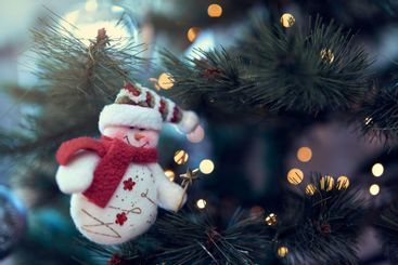 close up of snowman hanging on christmas tree with...