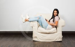 sitting on a white couch with phone