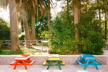 Three tables with benches of different colors. Street...