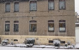Snow falling in front of an urban townhouse