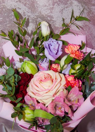 Delicate bouquet of different flowers in pink packaging.