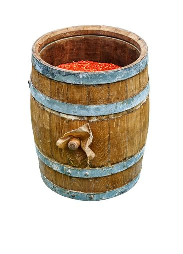 Open wooden barrel filled with hot pepper mash isolated...