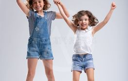 Two vivacious lively little girls jumping together