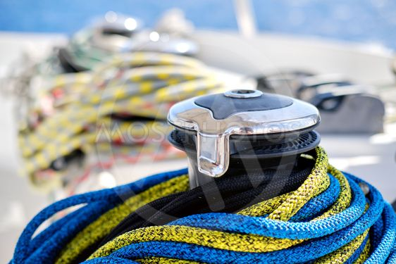 Winch with colourful yellow-blue rope on sailing...
