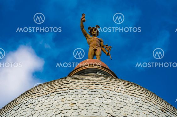 Statue of Mercury on top of the roof of a building in...
