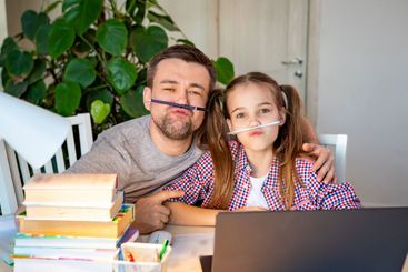 cheerful dad helps daughter distance learning home