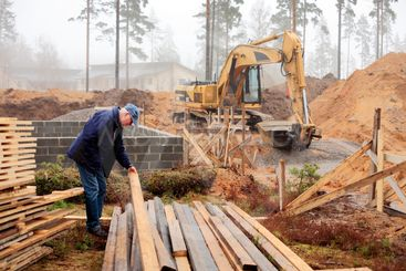 senior builder studying stacked timber in front of...