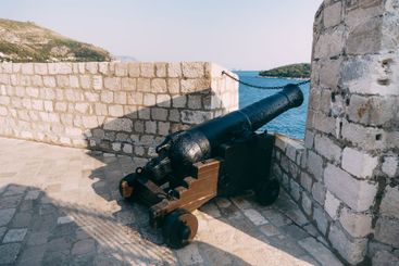 An ancient cannon with kernels on the wall of the old...
