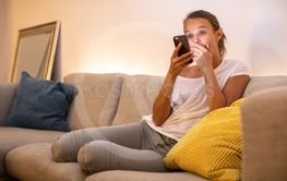 Cute young woman on a comfortable sofa in her modern...