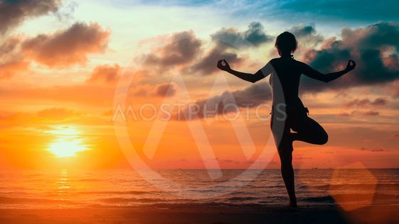 Surreal yoga silhouette of woman on the Sea beach.