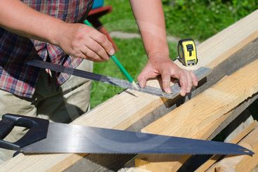 Male hands measuring and marking wooden plank outdoors