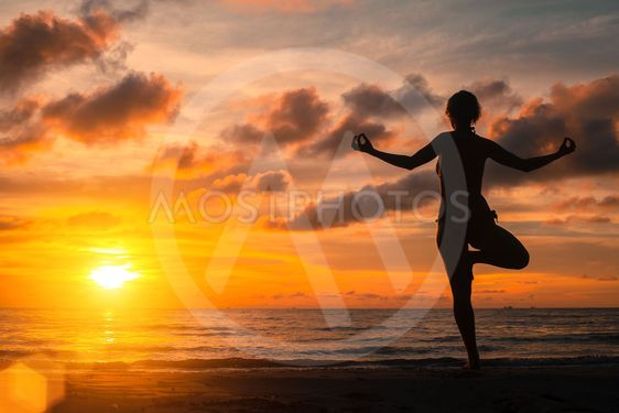 Yoga practicing at sunset, serenity and meditation.
