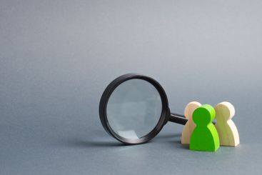Three wooden human figure stands near a magnifying glass...