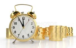 Golden alarm clock and stacks of golden coins. White...