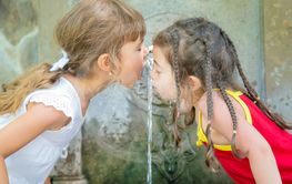children drink water from a spring in Borjomi, Georgia....