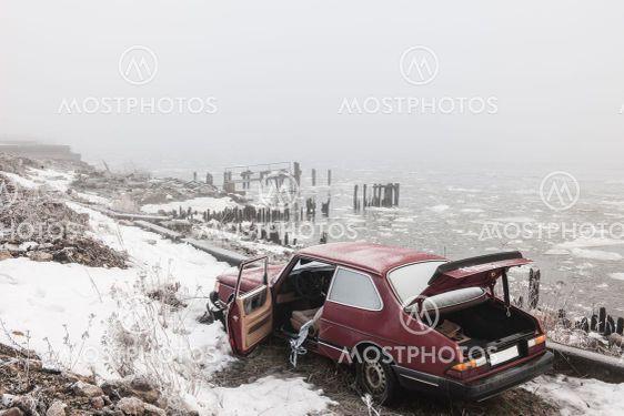 Abandoned car at winter river