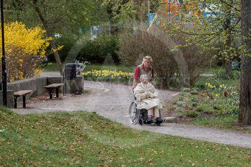 En äldre kvinna i rullstol får hjälp med att komma ut i...