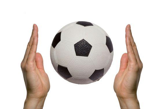 Fotbollen mellan två händer