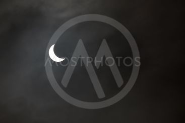 Partial solar eclipse in a grey misty sky