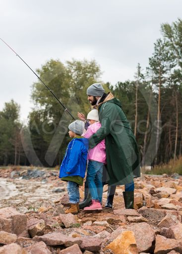 father and kids fishing together
