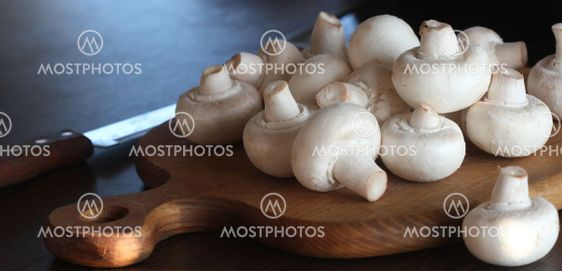 Food background of fresh champignons at the old cutting...
