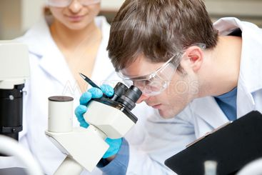 Caucasian male scientist holding pen and clipboard...