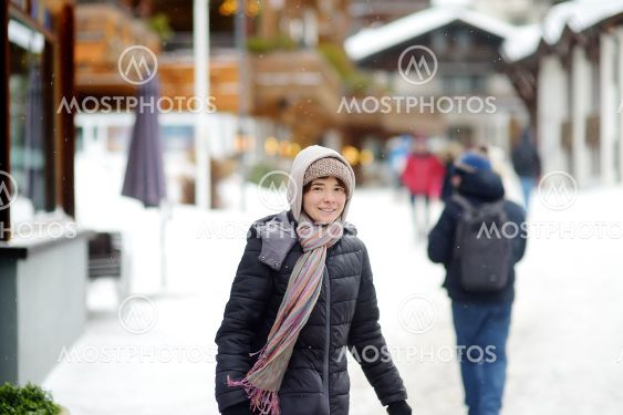 Young woman walking on street of mountain resort town in...
