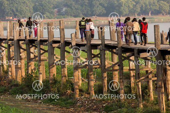 People crossing wooden bridge in Burma